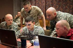 Five soldiers look at a laptop.