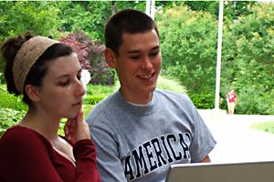Two students look at a laptop on American University's campus