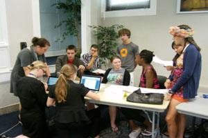 a large group of students all crowd around a table of computers