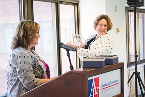 Dr. Carola Weil holds two crystal bookends behind a podium, smiling, in a polka dot blazer. To her left is Dr. Diane Lowenthal.