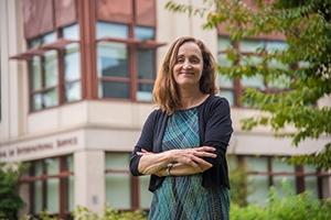 Professor Elizabeth Thompson stands in front of the School of International Service building.