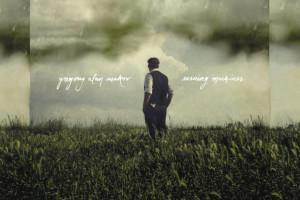 Album art from Gregory Alan Isakov album Evening Machines. Man standing in a field with clouds behind