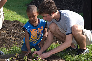 Photo: Anthony Kakoyannis helps a young member of Life Pieces to Masterpieces plant a flower in the new butterfly garden outside the Northeast Washington facility.