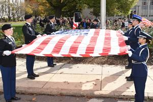 Men and women in military uniform holding the American flag.