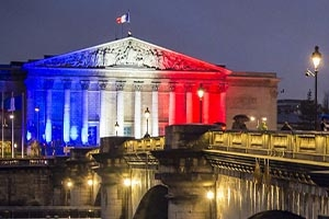 French National Assembly building lit up with blue, white, and red lights
