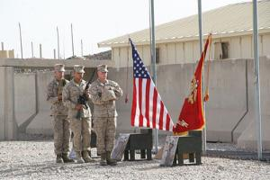 Marines with 2nd Combat Engineer Battalion carry combat boots, a rifle, and Kevlar helmet to build the battlefield cross in honor of three fallen Marines during a memorial ceremony aboard Camp Leatherneck, Afghanistan, July 8, 2014.