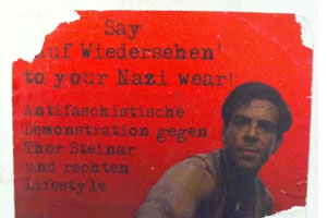 "A protest poster against white nationalist symbols. Man with a red backdrop. The German-to-English translation of this poster: ""Say goodbye to your Nazi wear: Anti-fascist demonstration against Thor Steinar and the right-wing lifestyle."""