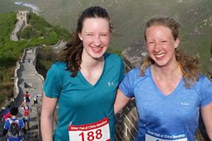 Two women in running clothes, standing at the Great Wall of China.