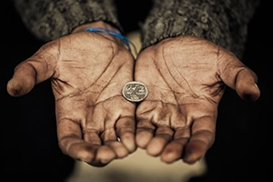 Outstretched hands of a poor man with a quarter between the palms.