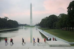 Runners on the Washington mall with Washington monument in background at sunset.