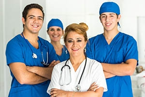 Four healthcare workers wearing scrubs.