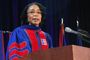 Woman with cap and gown at a podium while giving a speech.