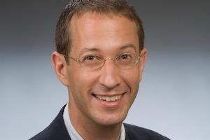 Headshot of Prof. Max Paul Friedman against a blue background.