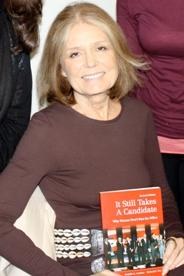 Gloria Stienem holding a copy of It Still Takes a Candidate