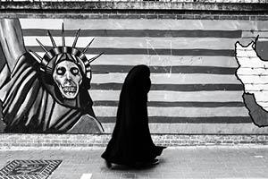 A woman walks in front of a mural in Tehran.