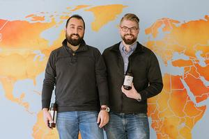 Two men posing in front of world map.