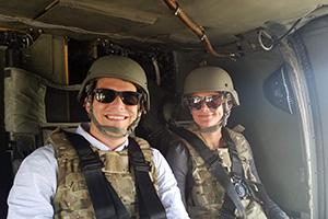 Two people wearing military uniforms in a helicopter