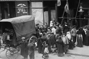 People next to a wagon, in front of a butcher shop.