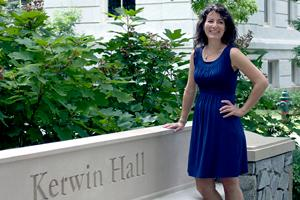 Female professor standing in front of the SPA Kerwin Hall sign.
