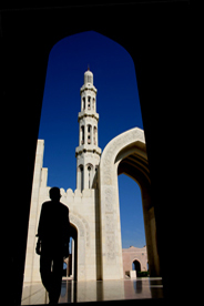 Man in shadow with sunlit mosque in the background.