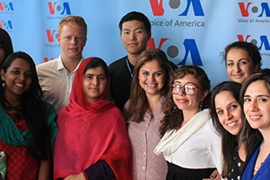 Malala Yousafzai in a red head scarf stands with a group of students, including Babu and Mammadova.