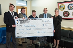 Campus Life Vice President Gail Hanson accepts donation check from Masonic and Eastern Star Home Charities representatives.