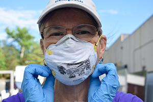 Lisa McGrail wears a mask and gloves while volunteering for Women Giving Back.