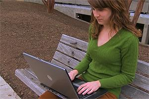 Francesca Morizio sitting on a bench and working on her laptop