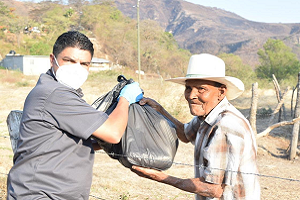 Man hands bag of donated food to another man