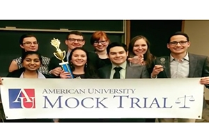 Mock Trial participants hold an American University Mock Trial banner.