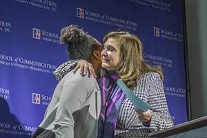 Professor Gemma Puglisi, right, hugs student award winner