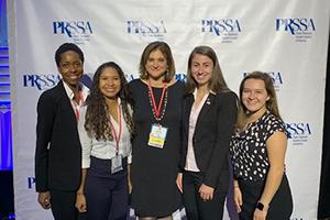 The PRSSA 2019 e board and Prof Puglisi standing in front of a plain backdrop