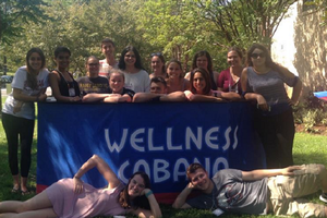 A group of students stand around the Wellness Cabana.