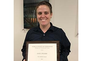 SPA Professorial Lecturer Jane Palmer holds her New Scholar Award.