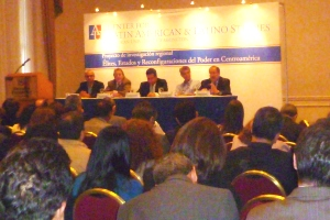 Five panelists sit at a table during a presentation
