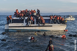 Syrian and Iraqi refugees wear life vests as they are rescued from a broken boat in the sea and arrive in Greece.