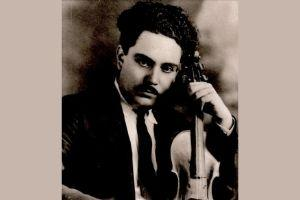 Man in jacket and tie holding a violin