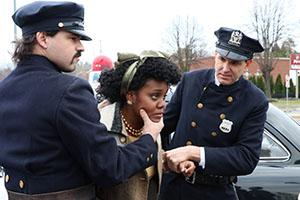 Two white police officers restrain a black woman.