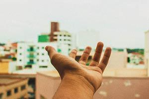 A hand is open toward a city.