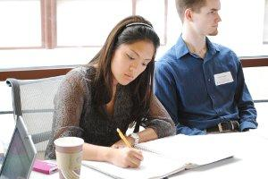 A student takes notes during a presentation.