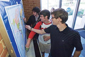 From left, Rob Masiello, Josh Jeffreys, and Phillip Ochs place their pins on the SIS map that shows where students and faculty have worked and studied.