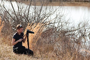 Woman with video camera on bank of bay