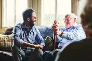 Doctor speaking with elderly man.