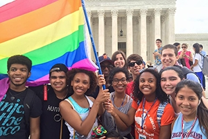 Students hold a rainbow pride flag in front of the Supreme Court.