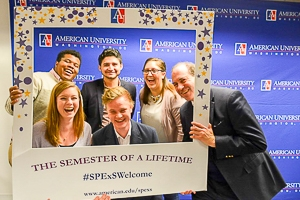 A group of students pose happily in front of an American University sign with their professor, holding a frame prop.