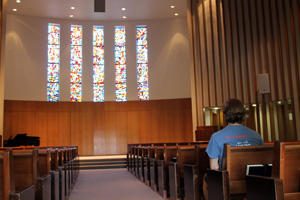 A student in deep thought while sitting in a pew at the Kay Spiritual Life Center