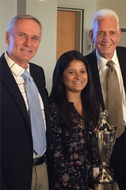 Rodger Streitmatter, Anagha Srikanth, and Thomas Grooms with the journalism award trophy.