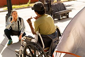 Director Laura Waters Hinson leans in front of a documentary subject, man in wheelchair