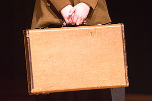 Woman's hands seen holding WWII era suitcase
