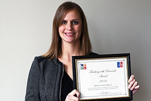 SPA Assistant Professor Tricia Bacon holds up her teaching with research award.